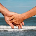 intimately holding hands at the ocean